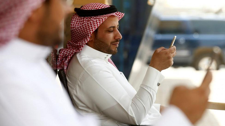 Saudi men explore social media on their mobile devices as they sit at a cafe in Riyadh